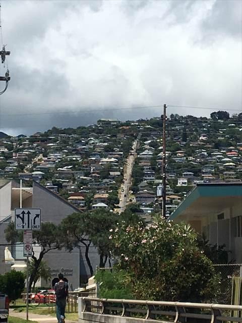 山のてっぺんまで家が立ち並ぶ中を通る急な坂道の道路